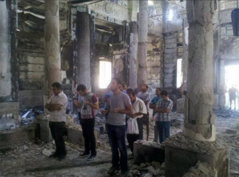 Copts worship in their burned out church sanctuary.