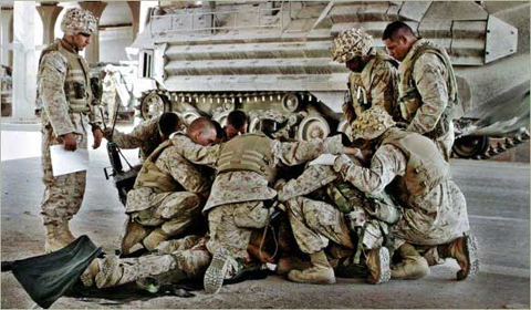 Deployed U.S. servicemen pause in prayer before a mission.