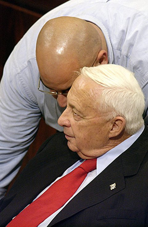 During Knesset debate, Prime Minister Ariel Sharon confers with his brother Omri (Israeli government photo)