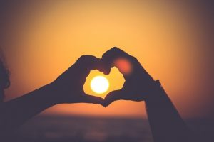 sunset-seen-through-hands-in-heart-shape