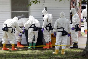 FILE - In this Friday, April 19, 2013 file photo, federal agents wearing hazardous material suits inspect a trash can outside the house of Paul Kevin Curtis