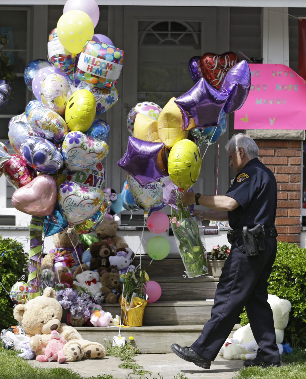 A Cleveland policeman carries balloons and flowers to the front porch of a home awaiting the arrival of Amanda Berry Wednesday, May 8, 2013