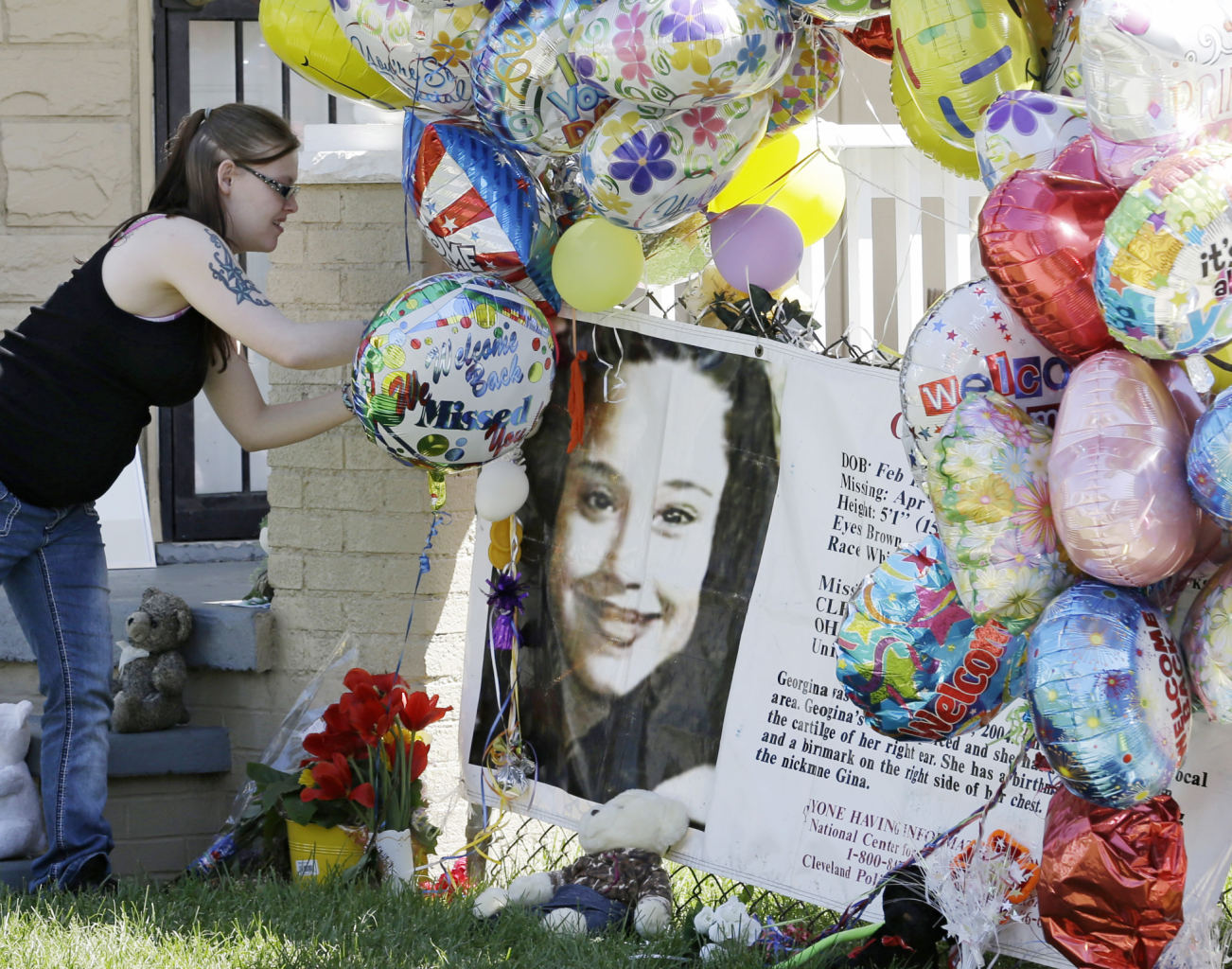 A girl adds a balloon outside the home of Gina DeJesus Thursday, May 9, 2013, in Cleveland