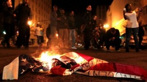American flag burns during a protest after George Zimmerman was found not