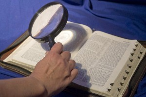 Bible with magnifying glass