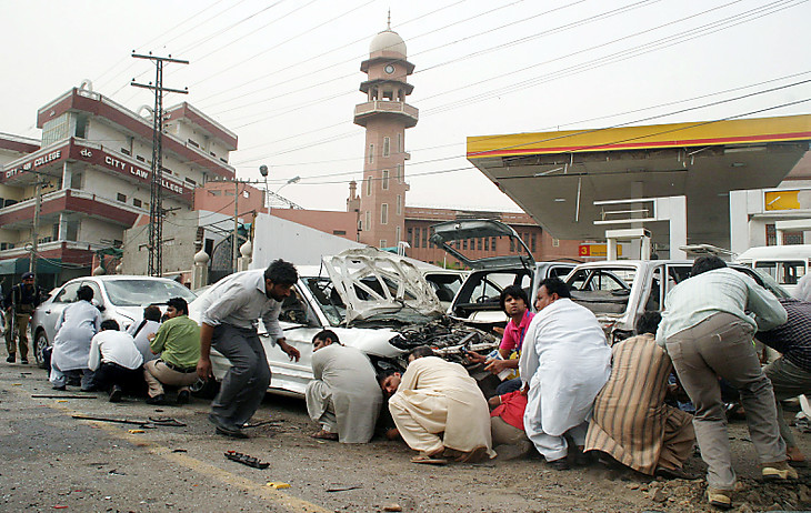 Pakistani media take cover outside one of two mosques stormed by gunmen in Lahore on May 28, 2010.  Gunmen dressed in suicide vests stormed two Pakistani mosques belonging to a minority sect in Lahore on May 28, killing at least 56 people and reducing prayers to a bloodbath, officials said. In one of the deadliest attacks in Pakistan's second city, which has been increasingly hit by Taliban and Al-Qaeda-linked violence, squads of militants stormed into prayer halls, firing off guns and grenades, and taking hostages. AFP PHOTO/ARIF ALI (Photo credit should read Arif Ali/AFP/Getty Images)(Photo Credit should Read /AFP/Getty Images)
